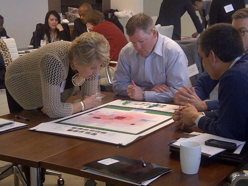 Sheila Ogle of Ogle Enterprises (Raleigh), left, Shane Douglas of Collier International (Nashville) and Juan Gonzalez of KeyBank Indiana (Indy) go through an exercise led by Jarrett Walker (@humantransit) where teams design a transit network for a fictional city with a set budget — one way to experience the real-life trade-offs that transit planners and cities have to make.