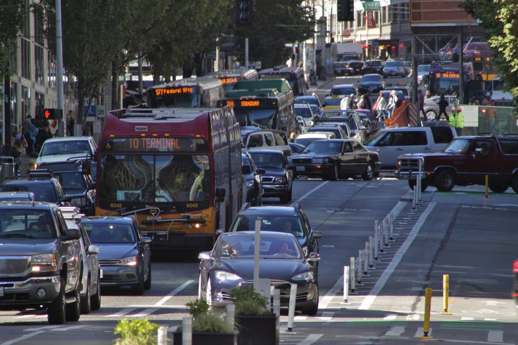 Metro busses navigate rush hour near downtown Seattle. The district has added thousands of jobs in recent years, but transit investments have kept single-rider car trips the same. Wikimedia photo by SounderBruce