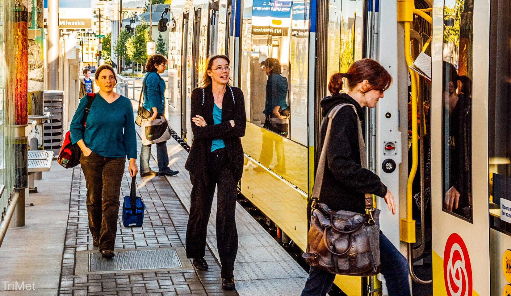 People boarding light rail in Portland, OR