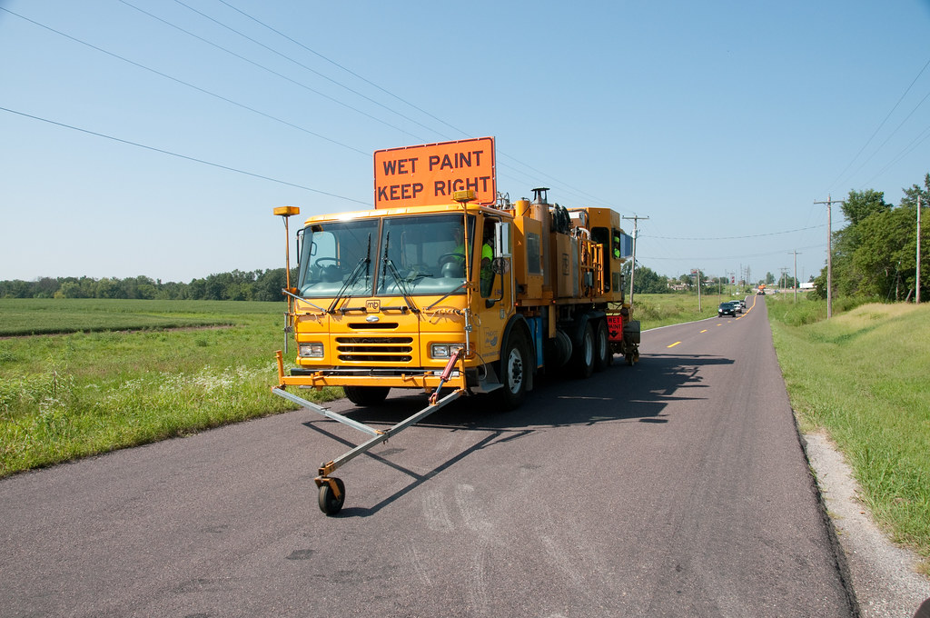 A truck painting lane markings on a two-lane road in Missouri.