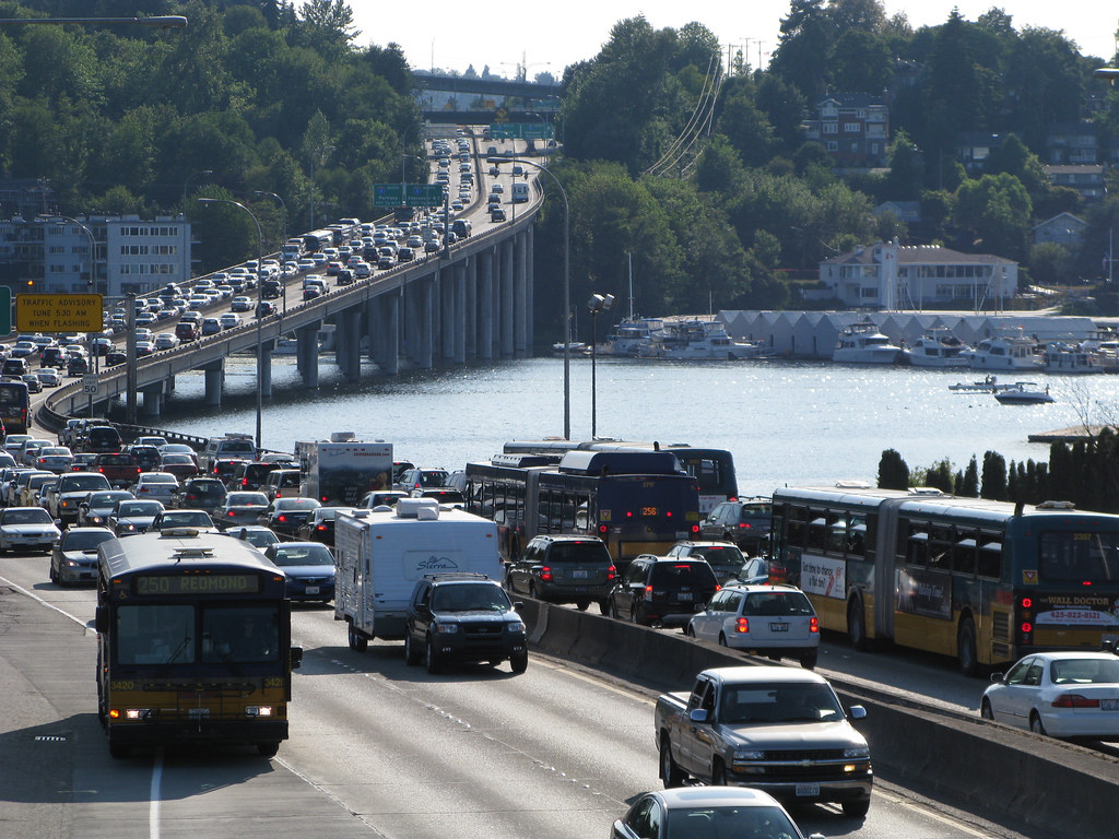 Vehicles moving slowly on a congested highway in Seattle. The highway crosses a narrow river.