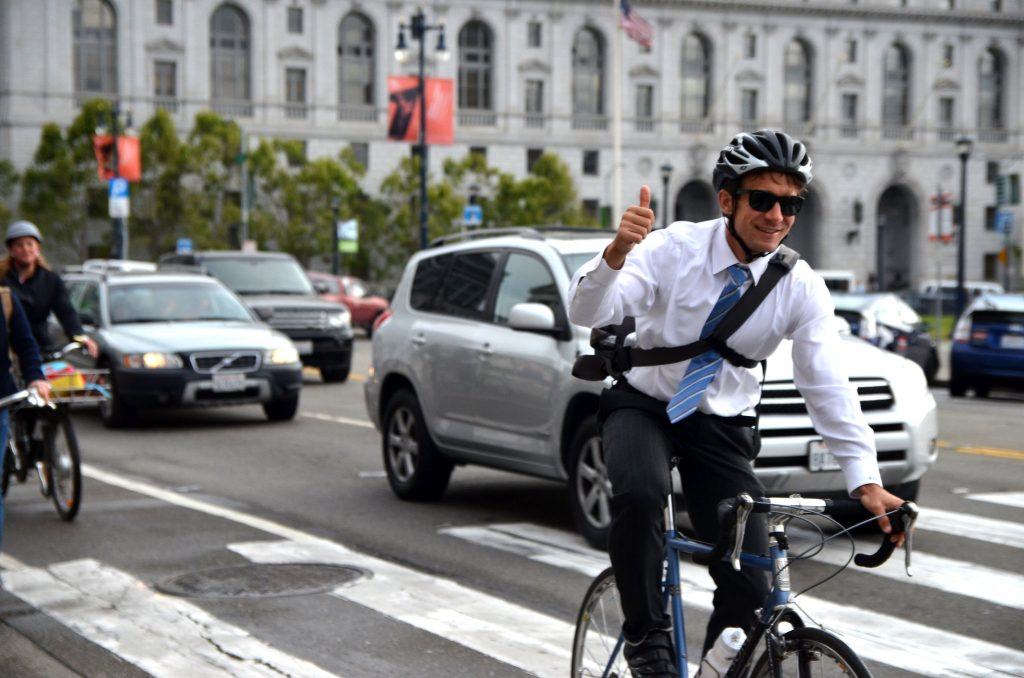 A bike commuter wearing a suit, tie, and a helmet flashes a thumbs up to the photographer while biking on a busy road in San Francisco.