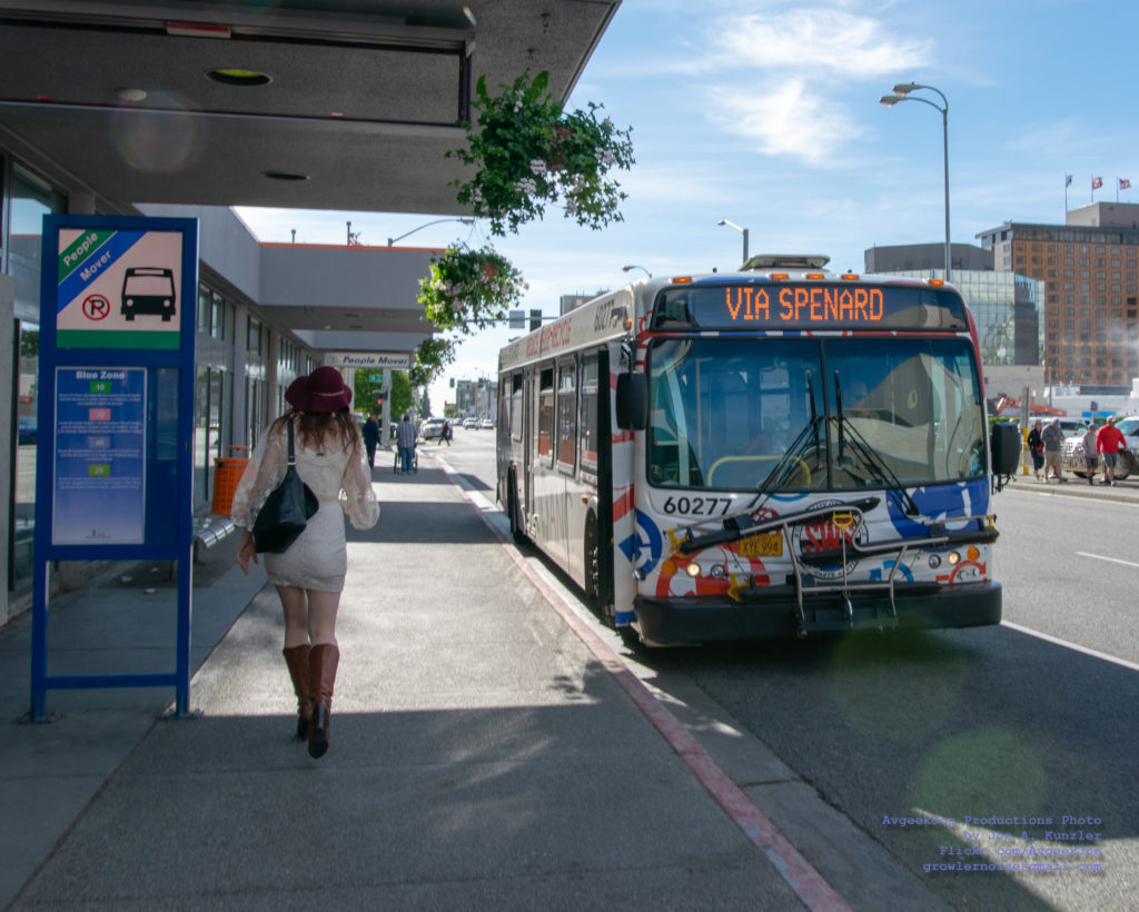 Woman walking by a bus stop in Anchorage, Alaska. The bus is stopped to pick up passengers.