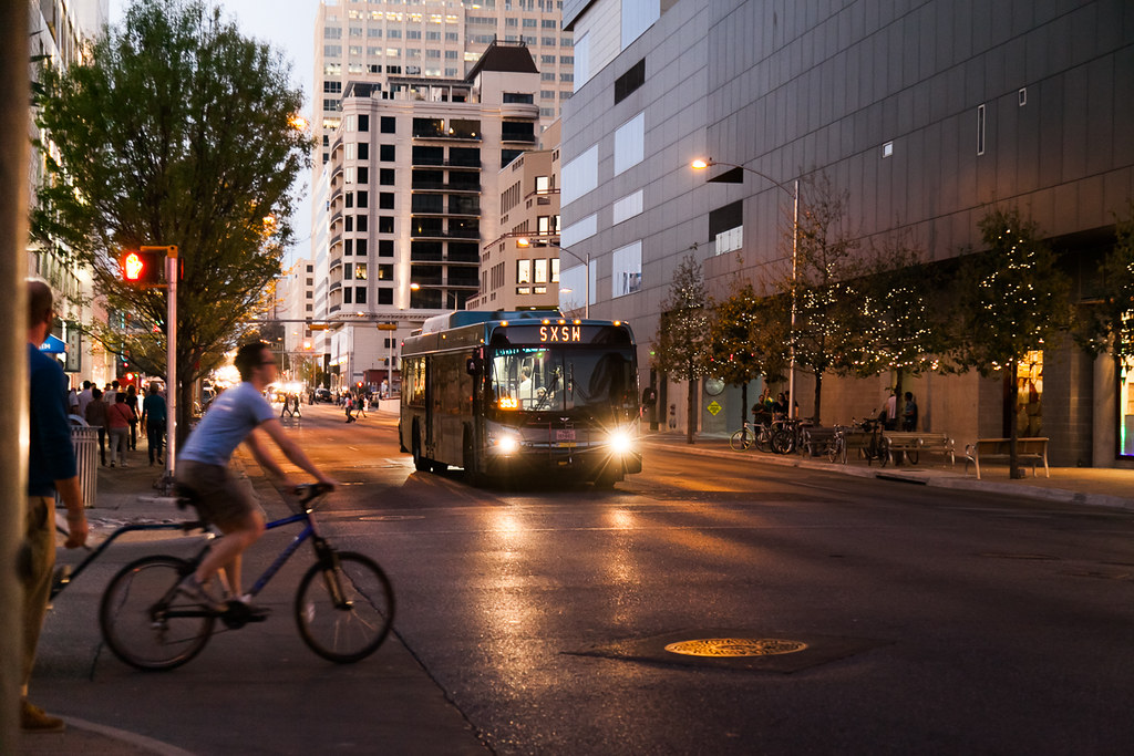A bus in Austin, Texas approaching an intersection at dusk. There is a bike rider crossing the street in the foreground.