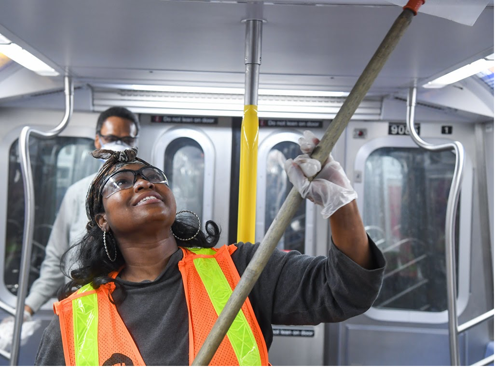 woman in MTA subway carriage cleaning the ceiling
